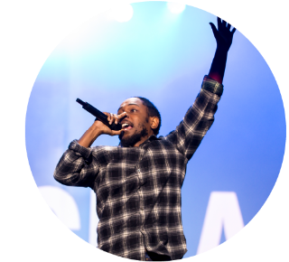 Kendrick Lemar onstage, holding a microphone to his mouth and holding his other hand in the air.