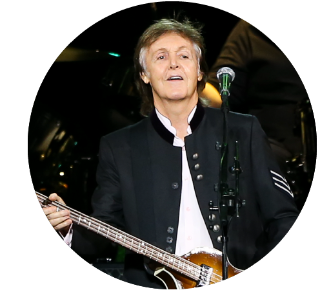 Paul McCartney smiling onstage while holding a bass guitar.