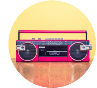 Pink, old-fashioned radio/cassette player with a handle on top.