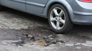 Close up of the rear left wheel of a car going into a large pothole in the road.