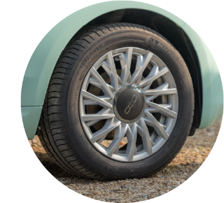 Close up of wheel on stationary car parked on gravel.