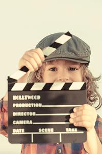 Boy holding a film set clapperboard