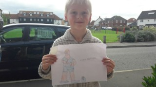 7-year-old Hayden holding up his drawing